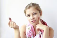 Chica joven con un caramelo en su mano Foto de archivo