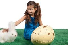 Chica joven con un conejito enorme de la dimensión de una variable y del juguete del huevo fotografía de archivo