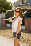 Chica joven con un monopatín al aire libre Fotos de archivo libres de regalías