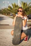 Chica joven con un monopatín al aire libre Fotografía de archivo