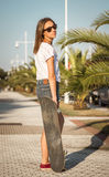 Chica joven con un monopatín al aire libre Imágenes de archivo libres de regalías