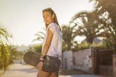 Chica joven con un monopatín al aire libre Fotografía de archivo libre de regalías