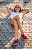 Chica joven con un monopatín que miente en la calle en verano Foto de archivo