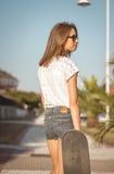 Chica joven con un monopatín que presenta en la calle Imágenes de archivo libres de regalías
