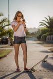 Chica joven con un monopatín usando el smartphone al aire libre Imagen de archivo libre de regalías