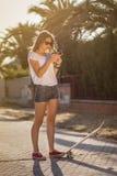Chica joven con un monopatín usando el smartphone al aire libre Imagenes de archivo