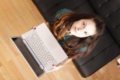 Chica joven con un ordenador portátil foto de archivo