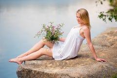 Chica joven con un ramo de wildflowers que asisten en la playa fotos de archivo