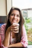 Chica joven con una bebida caliente Imagenes de archivo