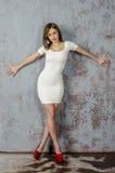 Chica joven con una figura hermosa en vestido blanco de moda en miniskirt ceñido y tacones altos y plataforma rojos vestidos Imágenes de archivo libres de regalías
