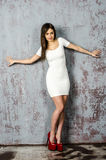 Chica joven con una figura hermosa en vestido blanco de moda en miniskirt ceñido y tacones altos y plataforma rojos vestidos Fotografía de archivo libre de regalías