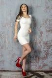 Chica joven con una figura hermosa en vestido blanco de moda en miniskirt ceñido y tacones altos y plataforma rojos vestidos Imagen de archivo libre de regalías