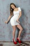 Chica joven con una figura hermosa en vestido blanco de moda en miniskirt ceñido y tacones altos y plataforma rojos vestidos Fotos de archivo
