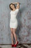 Chica joven con una figura hermosa en vestido blanco de moda en miniskirt ceñido y tacones altos y plataforma rojos vestidos Foto de archivo libre de regalías