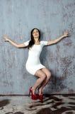 Chica joven con una figura hermosa en vestido blanco de moda en miniskirt ceñido y tacones altos y plataforma rojos vestidos Foto de archivo