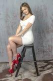 Chica joven con una figura hermosa en vestido blanco de moda en miniskirt ceñido y tacones altos y plataforma rojos vestidos Imagen de archivo