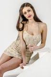 Chica joven con una figura hermosa en vestido de oro de moda en miniskirt y tacones altos y plataforma ceñidos Imágenes de archivo libres de regalías