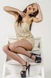 Chica joven con una figura hermosa en vestido de oro de moda en miniskirt y tacones altos y plataforma ceñidos Fotos de archivo libres de regalías
