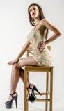 Chica joven con una figura hermosa en vestido de oro de moda en miniskirt y tacones altos y plataforma ceñidos Imagen de archivo libre de regalías