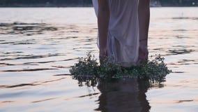Chica joven con una guirnalda en el río almacen de metraje de vídeo