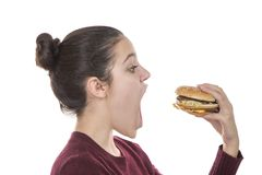Chica joven con una hamburguesa Foto de archivo