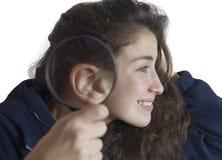 Chica joven con una lupa al lado de su oído Foto de archivo