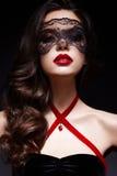 Chica joven con una máscara negra del cordón en su cara y un colgante bajo la forma de corazón en el cuello Modelo hermoso con ma Imagen de archivo