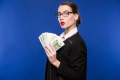 Chica joven con una pila de dinero en las manos de Imagen de archivo libre de regalías