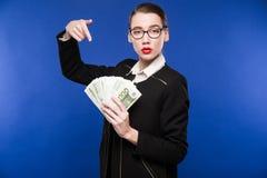 Chica joven con una pila de dinero en las manos de Imagenes de archivo