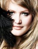 chica joven con una pluma cerca de su cara imagen de archivo