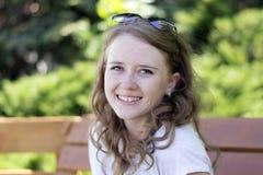 Chica joven con una sonrisa en el banco Imagenes de archivo