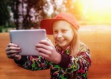 Chica joven con una tableta en el parque Imágenes de archivo libres de regalías