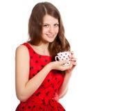 Chica joven con una taza de té en sus manos Imagen de archivo