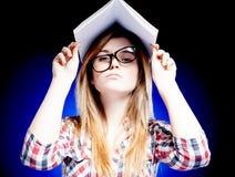 Chica joven confundida y desconcertada que sostiene el libro de ejercicio en su cabeza Foto de archivo libre de regalías