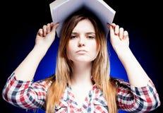 Chica joven confusa y trastornada que sostiene el libro de ejercicio en su cabeza Fotos de archivo libres de regalías