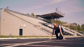 Chica joven, constitución deportiva, en el estadio Ella va a comenzar la línea, consigue en un comienzo bajo, y comienza a esprin almacen de video