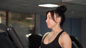 Chica joven conveniente para los ejercicios de funcionamiento en el gimnasio en la rueda de ardilla almacen de metraje de vídeo