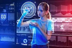 Chica joven curiosa que toca la pantalla mientras que analiza la proyección Imagen de archivo libre de regalías