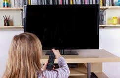 Chica joven dando vuelta con./desc. a la TV con un teledirigido Imagenes de archivo