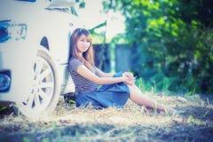 Chica joven de Asia en vestido con el coche de motor Imagen de archivo
