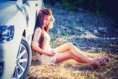Chica joven de Asia en vestido con el coche de motor Fotografía de archivo libre de regalías