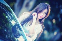 Chica joven de Asia en vestido con el coche de motor imagen de archivo libre de regalías