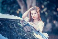 Chica joven de Asia en vestido con el coche de motor imagenes de archivo