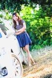 Chica joven de Asia en vestido con el coche de motor Imágenes de archivo libres de regalías