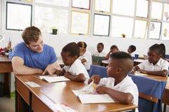 Chica joven de ayuda del profesor voluntario en su escritorio en clase imagen de archivo libre de regalías