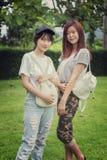 Chica joven de dos Asia con el bolso en parque fotografía de archivo