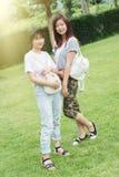 Chica joven de dos Asia con el bolso en parque imagenes de archivo