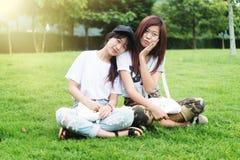 Chica joven de dos Asia con el bolso en parque imagen de archivo