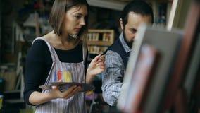 Chica joven de enseñanza del hombre experto del artista para dibujar pinturas y la explicación de los fundamentos en estudio del  imagen de archivo