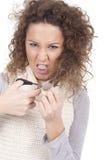 Chica joven de griterío que intenta cortar su pelo Fotografía de archivo